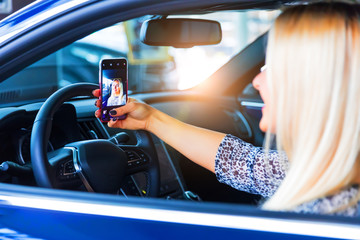 Young woman driver taking a selfie in her car