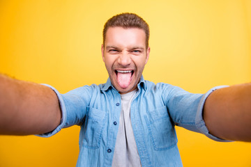 Self portrait of  attractive, crazy, cool man with bristle, stubble in jeans shirt, shooting selfie in two hands on front camera showing tongue out over yellow background