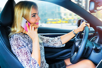 Young woman driver talking by phone in the car