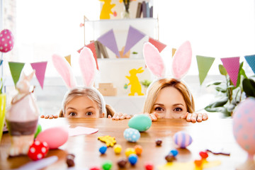 Two cute little sisters, friends wearing bunny ears, rabbit costumes, playing egg hunt on Easter, adorable child with mother celebrate Easter at home, looking out table