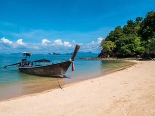 Long thail boat on the beach of an empty island Koh Nok in Thailand.
