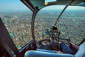 Helicopter cockpit inside the cabin flying on Tokyo cityscape. Sumida District, Japan. Sunny day.