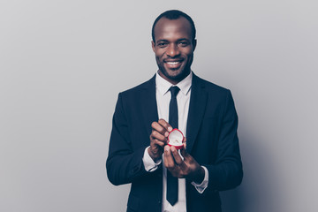 Will you be my woman wife? Portrait of happy smiling excited romantic loving afro guy making an offer marriage opening red box with diamond golden ring isolated on gray background