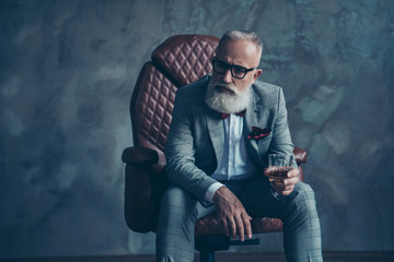 Minded, ponder, unhappy rich man in glasses, hold glass with cognac, in tuxedo with red bowtie and pocket square, sit in leather chair over gray background, looking to the side, shares, stock, money