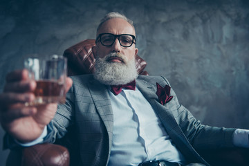 Attractive, old investor in spectacles, hold glass with brandy, in tuxedo with red bowtie and pocket square, sit in leather chair over gray background, looking at the camera, shares, stock, money