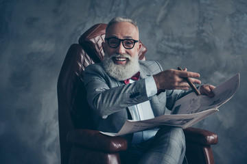 Attractive, rich, old, laughing boss with beaming smile in glasses, tux with red bow, have, hold newspaper, smoke cigarette, sitting in leather armchair in workplace over gray background, relax, fun