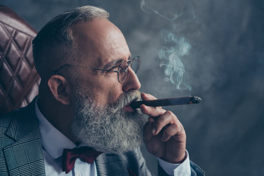 Side view close up of brutal harsh professional investor, shareholder smoking cigar over gray background
