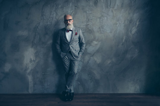 Full length portrait of stunning perfect brutal harsh old man in suit with bow-tie holding hands in pockets, leg by foot standing on wooden floor over gray wall