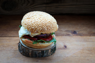 hamburger buns with sesame seeds, arugula, egg, cutlet lies on the stand of natural wood on a dark background