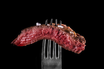 Photo sur Aluminium Viande Beef meat rare on fork black background