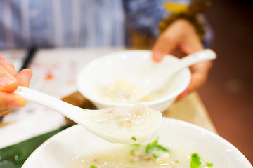 Woman fill a bowl with porridge in restaurant