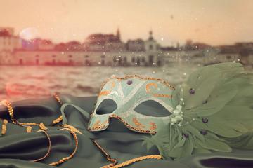 Wizerunek elegancka venetian maska na jedwabniczej tkaninie przed rozmytym Wenecja tłem.