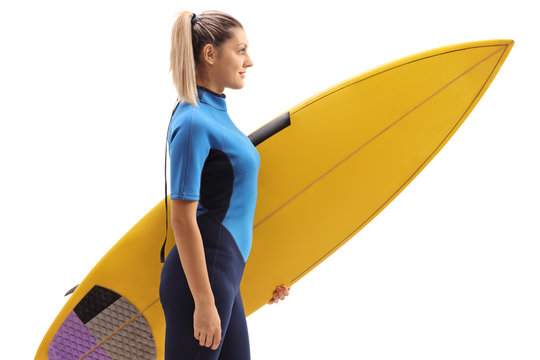 Profile shot of a female surfer with a surfboard