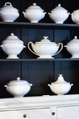 Black kitchen cabinet with a collection of white porcelain soup tureens