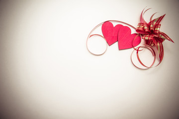 two red hearts and ribbon on white background