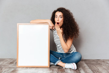Funny portrait of adult girl in jeans sitting in lotus pose on the floor expressing embarrassment and surprise while holding picture in frame copy space