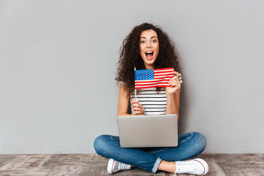 Gorgeous female with beautiful smile sitting in lotus pose with silver computer on legs demonstrating american flag on camera over grey wall