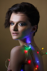 Fashion beauty portrait of a beautiful girl with a shiny make-up with a garland of colorful lights.