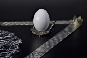 white egg on a silver stand royal award, black background