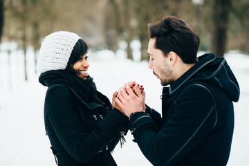 Young man warming girlfriend's hands in the winter