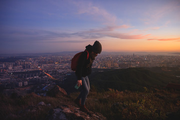 Girl taking pictures of beautiful sunset on mountain top