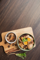 Pha-lo : Eggs boiled and pork boiled with spices  and fried tofu in sweet gravy soup on wooden background with copy space