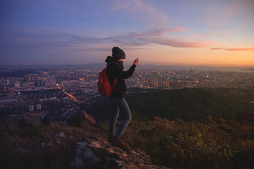 Girl taking pictures of beautiful sunset view with city lights below