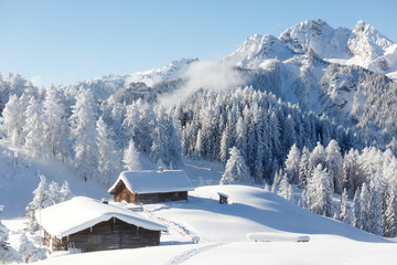Winter wonderland in Austrian Alps. Beautiful winter scenery with frozen trees and traditional alpine hut
