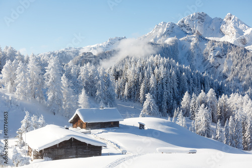 Fototapete Winter wonderland in Austrian Alps. Beautiful winter scenery with frozen trees and traditional alpine hut