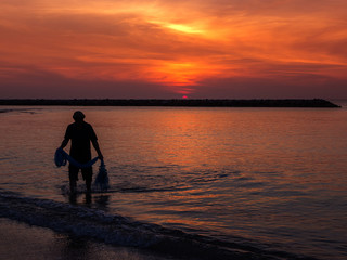 Fishermen are fishing in the sea on sunrise time.