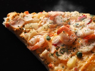 Close up delicious of seafood pizza over dark background.