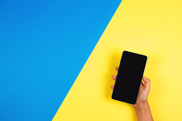 Hand holding the phone on blue and yellow background