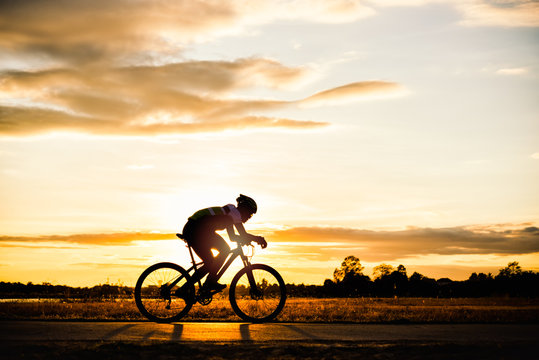 Silhouette man cycling at sunset