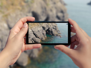A woman take a travel picture of the sea and diving people. A man jumps into the water in a picture of a smartphone