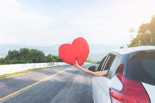 Young asian girl holding red heart and Reach out of the car at sunset