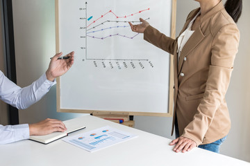 Business woman leader making presentation with her colleagues, pointing to the graph on board and business strategy during meeting in modern office
