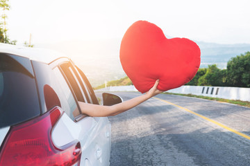 Relaxed happy traveler, Young beatiful asian gilr holding red heart and Reach out of the car at sunset and beautiful view with mountain road background