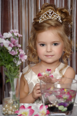 Little girl in white dress with diadem