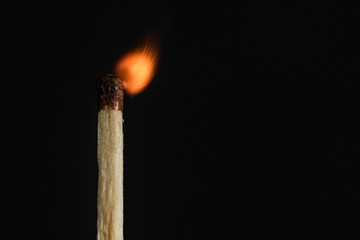 The time of the decay of the dying match flames on a black background closeup
