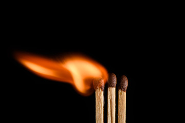 Three matches and one of them is in the process of ignition on a black background closeup
