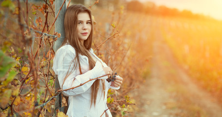 A half-naked brunette girl in a white vintage blouse and long hair posing against the background of an autumn vineyard. Holds a bunch of grapes in the rays of a bright sun. Vintage color tone