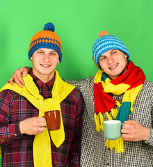 Twins with cheerful faces hold cups. Autumn season and friendship.