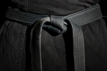 Black judo, ju-jitsu, or karate belt on a black kimono