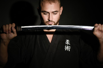 man practicing ju-jitsu in a black kimono carrying a japanese sword, called laïto
