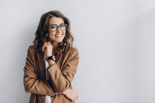 Emotional portrait of a beautiful and smiling girl in a glasses which stands near a white wall. Blank space for a text