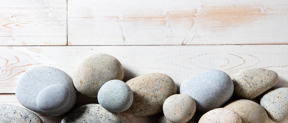 border of grey zen stones set on white wooden background