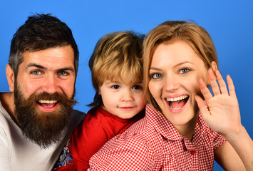 Mother, father and son with smiling faces hug on blue