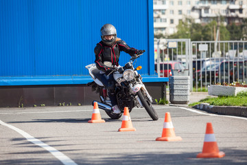 L-driver person driving slalom through the orange cones on motordrome on motorcycle