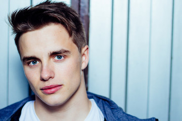 Portrait of attractive young man with blue eyes and metallic door background. Copy space.