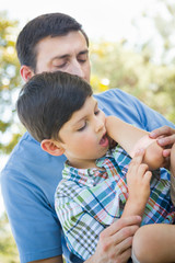 Loving Father Puts a Bandage on the Elbow of His Young Son in the Park.